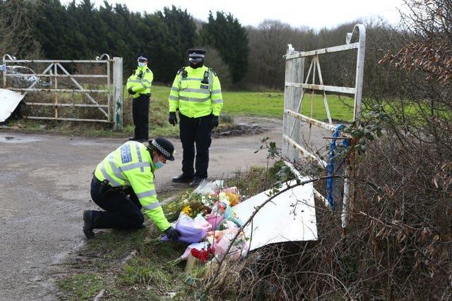 A police officer places flowers left by members of the public at the site as Metropolitan Police continue their search near Great Chart, Kent