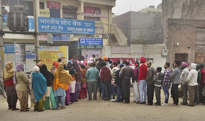 (File photo) Despite cold weather people queuing outside the State Bank of India branch to get cash at Batala Road on December 29, 2016 in Amritsar, India. (Photo by Sameer Sehgal/Hindustan Times via Getty Images)