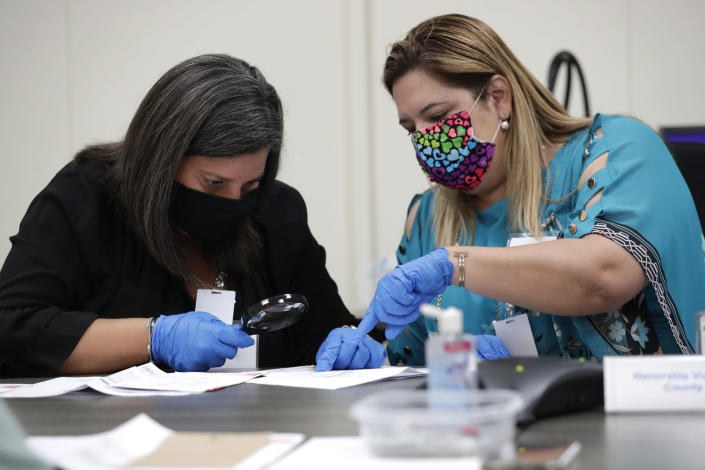 """Miami-Dade County Judges Eleane Sosa-Bruzon, left, and Victoria Ferrer, right, examine signatures on vote-by-mail ballots for the August 18 primary election as the canvassing board meets at the Miami-Dade County Elections Department, Thursday, July 30, 2020, in Doral, Fla. President Donald Trump is for the first time publicly floating a """"delay"""" to the Nov. 3 presidential election, as he makes unsubstantiated allegations that increased mail-in voting will result in fraud. (AP Photo/Lynne Sladky)"""