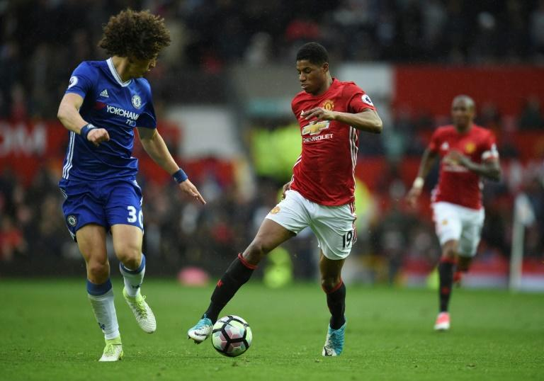Manchester United's striker Marcus Rashford (R) takes on Chelsea's defender David Luiz (L) during the English Premier League football match between Manchester United and Chelsea at Old Trafford in Manchester, north west England, on April 16, 2017