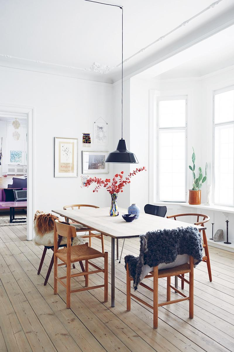 """From The Scandinavian Home: Interiors Inspired by Light. Karen Maj Kornum. Designer: Karen Maj's dining table. """"I would never place eight identical chairs around a table."""""""