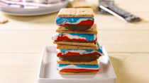 """<p>What could be better than a classic s'more? A s'more with red, white, and blue marshmallow filling, of course. </p><p><strong><em>Get the recipe for <a href=""""https://www.delish.com/cooking/recipe-ideas/a21970312/star-spangled-s-mores-recipe/"""" rel=""""nofollow noopener"""" target=""""_blank"""" data-ylk=""""slk:Star Spangled S'more Cookies"""" class=""""link rapid-noclick-resp"""">Star Spangled S'more Cookies</a>. </em></strong></p>"""
