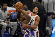 Sacramento Kings forward Harrison Barnes, left, is fouled by Portland Trail Blazers guard CJ McCollum, right, during the first quarter of an NBA basketball game in Sacramento, Calif., Wednesday, Jan. 13, 2021. (AP Photo/Rich Pedroncelli)