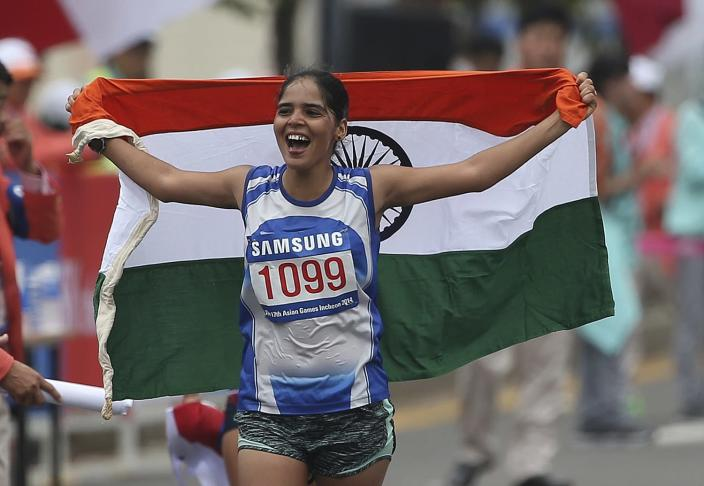 India's Kaur Khushbir holds her national flag after taking second place in the women's 20km race walk at the 17th Asian Games in Incheon, South Korea, Sunday, Sept. 28, 2014.(AP Photo/Rob Griffith)
