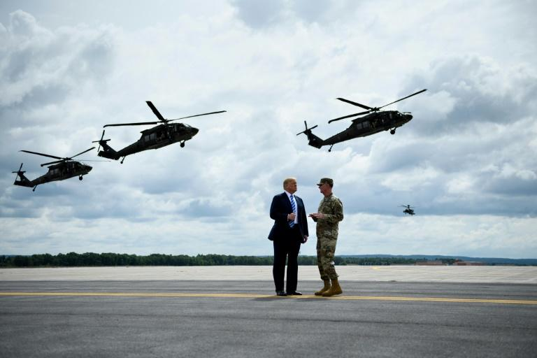 US President Donald Trump (L) reveres all things military -- here, he watches an air assault exercise with Army Major General Walter Piatt at Fort Drum, New York, on August 13, 2018