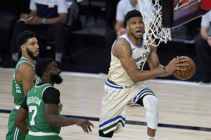 Milwaukee Bucks' Giannis Antetokounmpo, right, heads to the basket past Boston Celtics' Jaylen Brown (7) during the first half of an NBA basketball game Friday, July 31, 2020, in Lake Buena Vista, Fla. (AP Photo/Ashley Landis, Pool)