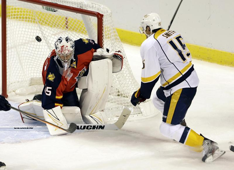 Florida Panthers goalie Michael Houser (35) deflects a shot by Nashville Predators center Craig Smith (15) during the third period of an NHL preseason hockey game, Monday, Sept. 16, 2013, in Sunrise, Fla. The Panthers won 3-2 in overtime. (AP Photo/Alan Diaz)