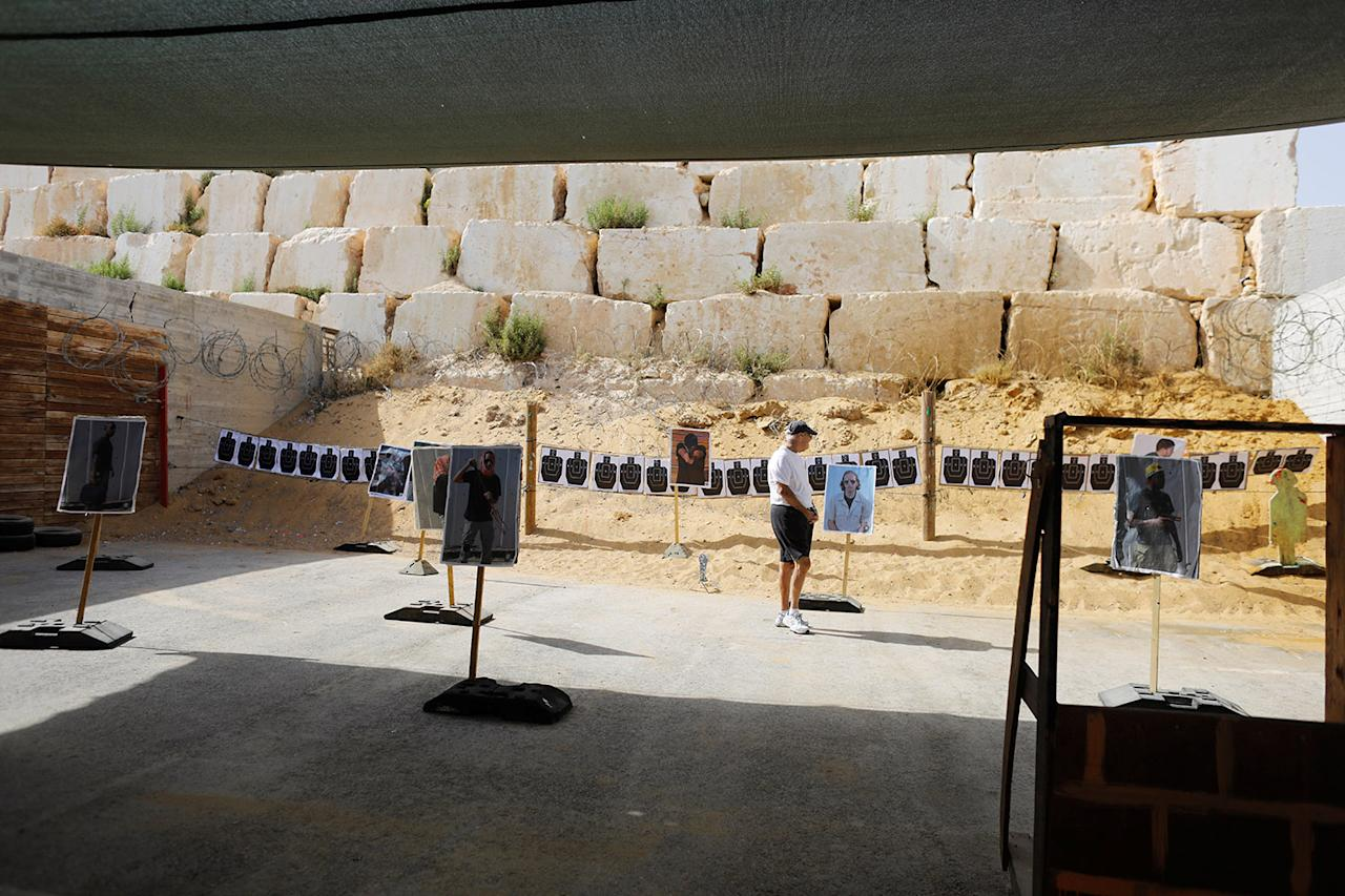 "<p>A tourist looks at posters placed near shooting targets during a two hour ""boot camp"" experience, at ""Caliber 3 Israeli Counter Terror and Security Academy"" in the Gush Etzion settlement bloc south of Jerusalem in the occupied West Bank July 13, 2017. (Photo: Nir Elias/Reuters) </p>"
