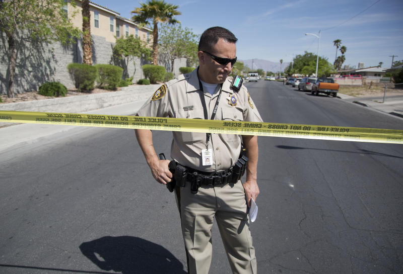Las Vegas Metro police officer Jacinto Rivera confirms for members of the media that two bodies and an injured man were found inside a home, Monday, April 16, 2012, in Las Vegas. Police are questioning a man covered in blood at the home where a 9-year-old boy told school officials his mother and sister were dead. (AP Photo/Julie Jacobson)