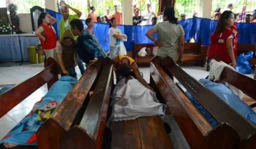 People weep next to the bodies of victims of a landslide in Naga City, on the popular tourist island of Cebu