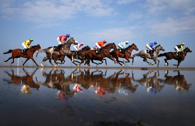 Runners and riders reflect in the water while competing in the Barry Matthews Appreciation Society Handicap during the 2014 Laytown Races held in County Meath Ireland. The historic race meeting, which takes place on a beach, was first held in 1868