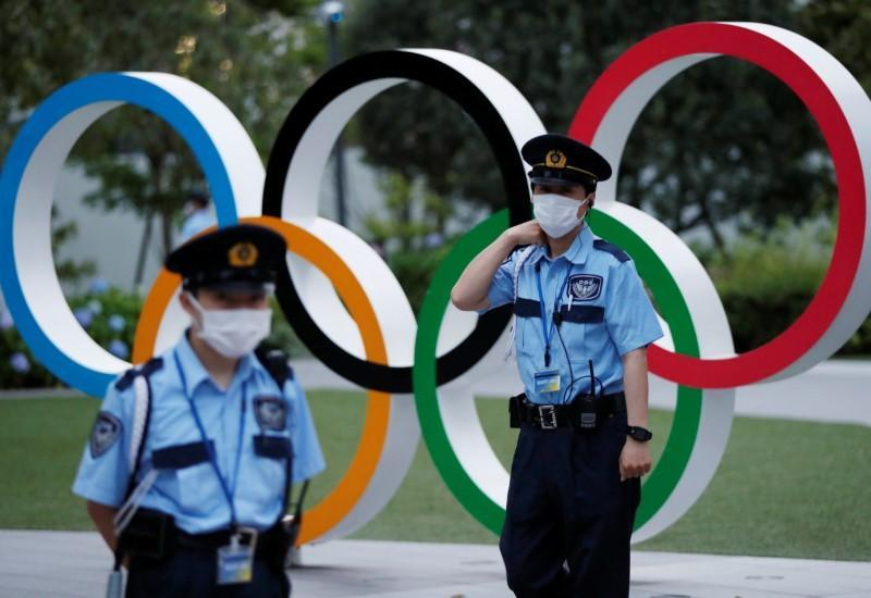 Security officers stand guard next to Olympic Rings monument during an anti-Olympics rally in Tokyo