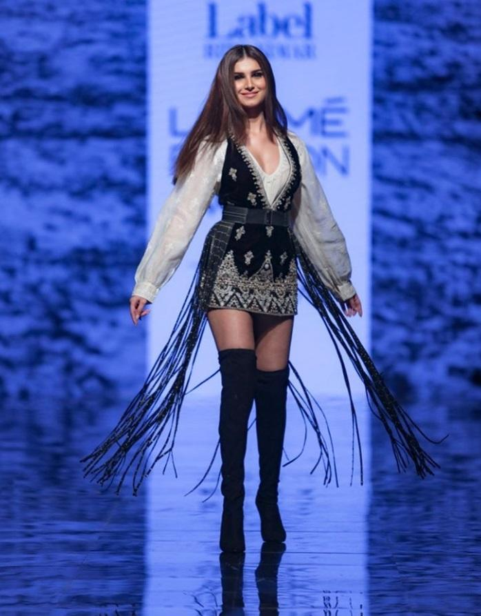The young entrant to Bollywood makes her LFW debut in a chic <strong>Ritu Kumar </strong>creation. The fun outfit in monochrome was teamed up with thigh-high boots and a decorative belt featuring trailing fringes. Blow-dried straight hair and nude make-up went well with the overall look.