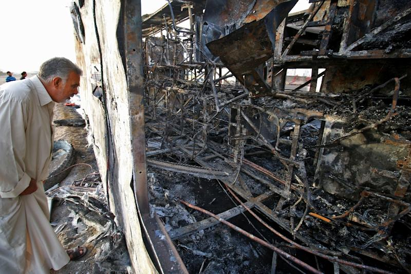 An Iraqi man inspects the wreckage of a bus that was damaged in a car bomb attack, in the southern Iraqi city of Basra on May 20, 2017