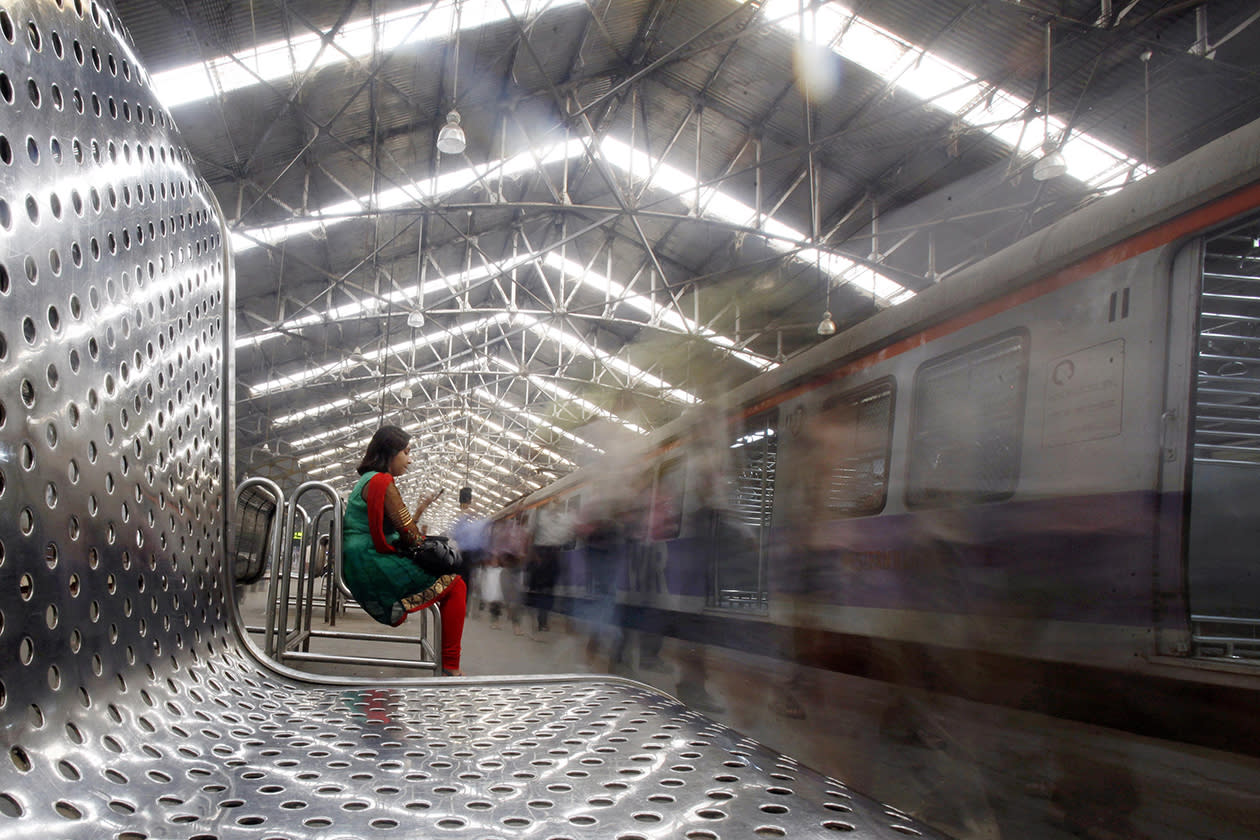 A woman checks her mobile phone at a train station in Mumbai, India.