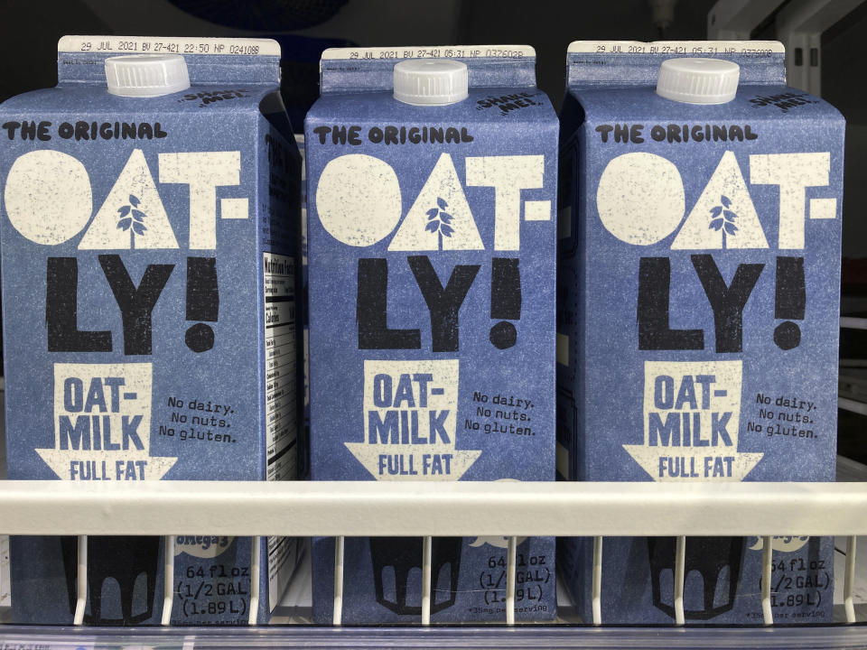 Three Oatly oat milk containers on a grocery store shelf.