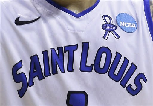 A ribbon for former head coach Rick Majerus is shown on the jersey of Saint Louis forward Grandy Glaze (1) during the first half of a second-round game in the NCAA college basketball tournament against New Mexico State in San Jose, Calif., Thursday, March 21, 2013. (AP Photo/Jeff Chiu)