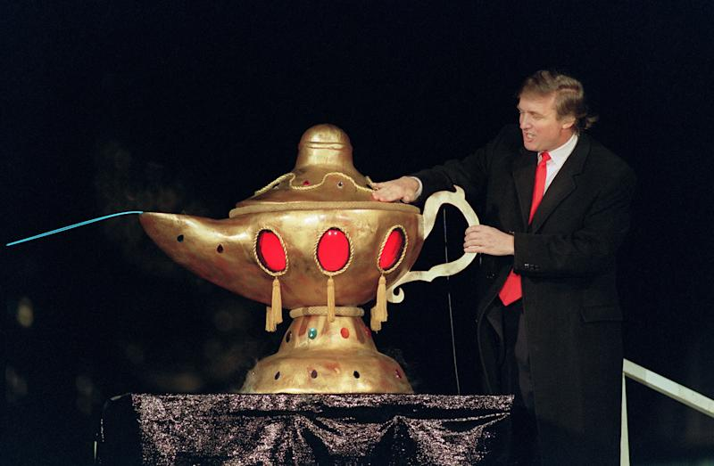 """Real estate developer Donald J. Trump rubs a """"magic lamp"""" during the opening ceremony for his huge Taj Mahal casino, in Atlantic city, 05 April 1990. Billionaire Donald Trump, who was born in 1946, Queens, New York, has gained notability for his celebrity lifestyle and his real estate successes. / AFP PHOTO / BILL SWERSEY (Photo credit should read BILL SWERSEY/AFP/Getty Images)"""
