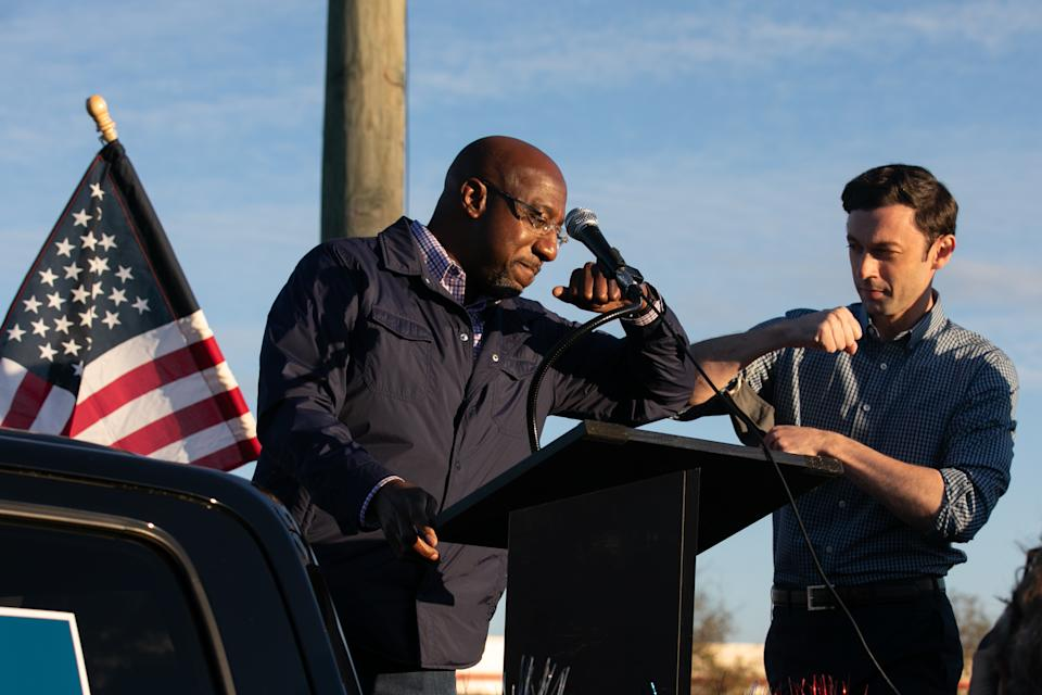 Georgia Democratic U.S. Senate candidates Jon Ossoff (R) and Raphael Warnock (L) taps elbows during a rally for supporters on November 15, 2020 in Marietta, Georgia. (Jessica McGowan/Getty Images)