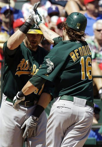 Oakland Athletics' Josh Reddick (16) celebrates with Jonny Gomes after Reddick's solo home run during the seventh inning of a baseball game against the Texas Rangers, Thursday, May 17, 2012, in Arlington, Texas. The Athletics won 5-4 in the 10th inning. (AP Photo/LM Otero)