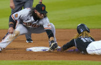 San Francisco Giants shortstop Brandon Crawford (35) tags out Colorado Rockies' Raimel Tapia (15) on an attempted steel during the fifth inning of a baseball game, Wednesday, Aug. 5, 2020, in Denver. (AP Photo/Jack Dempsey)