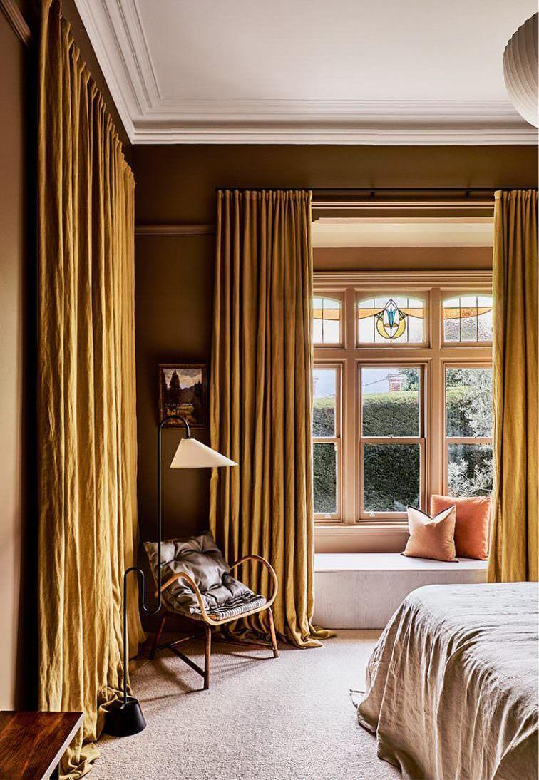 """<p>Chocolate brown walls and peach throw pillows in this majestic and calming bedroom designed by <a href=""""https://fionalynch.com.au/"""" rel=""""nofollow noopener"""" target=""""_blank"""" data-ylk=""""slk:Fiona Lynch"""" class=""""link rapid-noclick-resp"""">Fiona Lynch</a> accentuate the colors in the stained glass window, exemplifying that it's best to celebrate rather than fight with pre-existing quirks. </p>"""