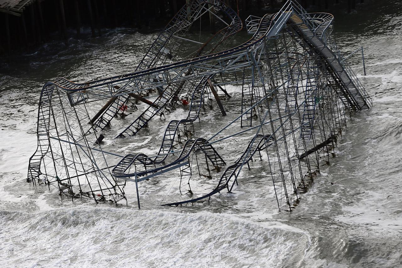 "Seaside Heights Police Chief Thomas Boyd told the Associated Press, ""We have to get everyone off the island because there is total  devastation."" Here, surf rolls past a destroyed roller coaster in this close-up view of the wrecked Seaside Heights, N.J., amusement park. (Mario Tama/Getty Images)"