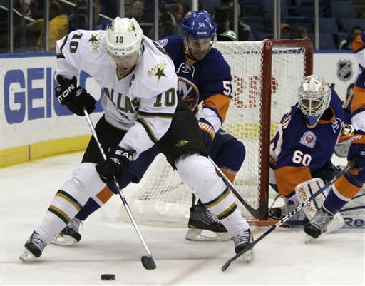 New York Islanders center Frans Nielsen (51) defends as Dallas Stars left wing Brenden Morrow (10) tries to control the puck while Islanders goalie Kevin Poulin keeps an eye on the play in the first period of their NHL hockey game at Nassau Coliseum in Uniondale, N.Y., Thursday, Dec. 15, 2011. (AP Photo/Kathy Willens)