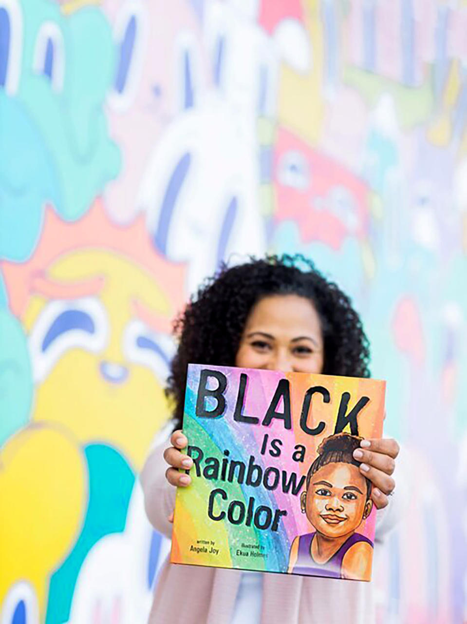 """In this November 2019 photo provided by Blossom Blue Studios, author Angela Joy poses with her 2020 book, """"Black is a Rainbow Color,"""" in Long Beach, Calif. Seeing the lack of diversity in children's books, Joy said she felt a responsibility to her community to write this book. (BlossomBlueStudios.com via AP)"""
