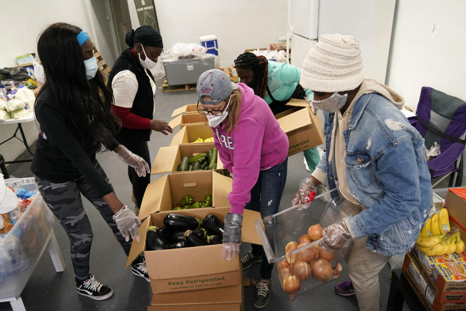 Sherina Jones, left, works with volunteers organizing food for distribution, Wednesday, Dec. 9, 2020, in the Liberty City neighborhood of Miami. (AP Photo/Lynne Sladky)