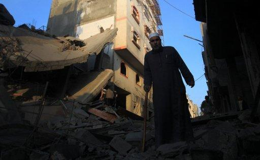 A Palestinian walks amongst the debris of destroyed homes following an Israeli air strike in Gaza City. Israeli strikes killed 32 Palestinians on Monday, taking the Gaza death toll to 109 as UN chief Ban Ki-moon joined efforts to end the worst violence in four years and Israel's inner circle of ministers mulled their next move