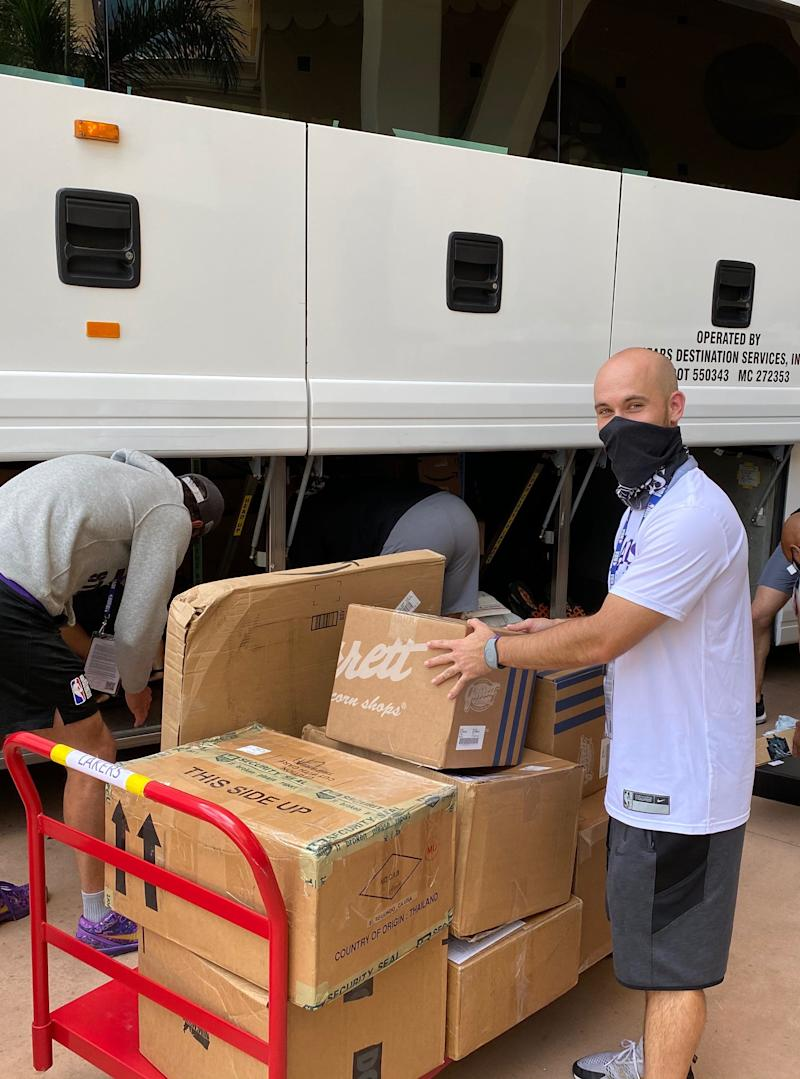 Equipment manager Andrew Henk helps load items into the Los Angeles Lakers' team bus in Orlando. The former Michigan State team manager and Pistons' assistant equipment manager finished his first year with the NBA champion Lakers.