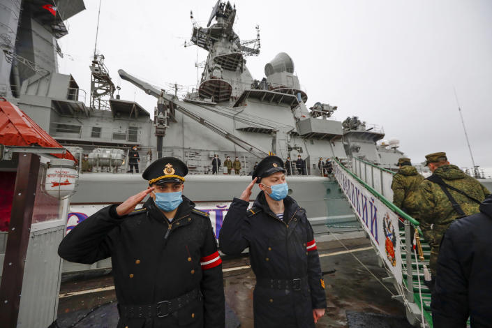 Russian sailors salute as they stand guard at the Northern Fleet's flagship, the Pyotr Veilikiy (Peter the Great) missile cruiser, at its Arctic base of Severomorsk, Russia, Thursday, May 13, 2021. Adm. Alexander Moiseyev, the commander of Russia's Northern Fleet griped Thursday about increased NATO's military activities near the country's borders, describing them as a threat to regional security. (AP Photo/Alexander Zemlianichenko)