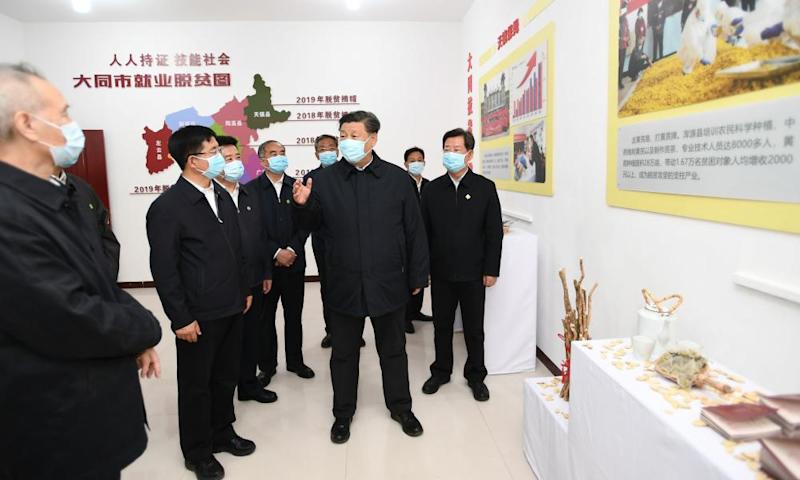 China's president, Xi Jinping, with a group of men all in masks