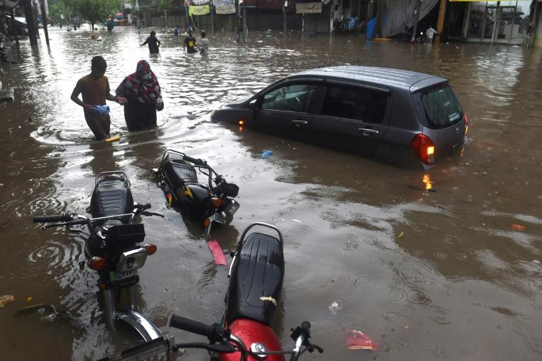 Lahore residents wade through a flooded street after heavy monsoon rains in the Pakistan city