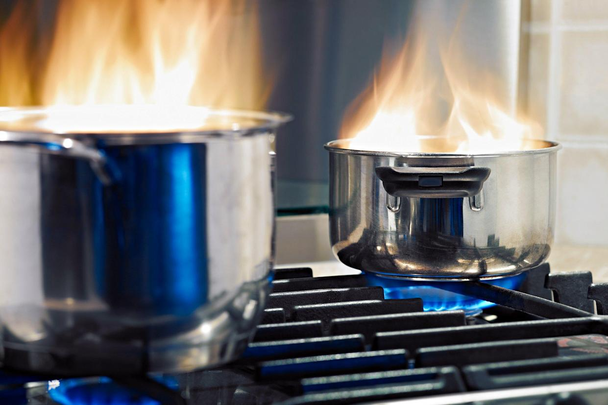 Two pots on fire on a stove