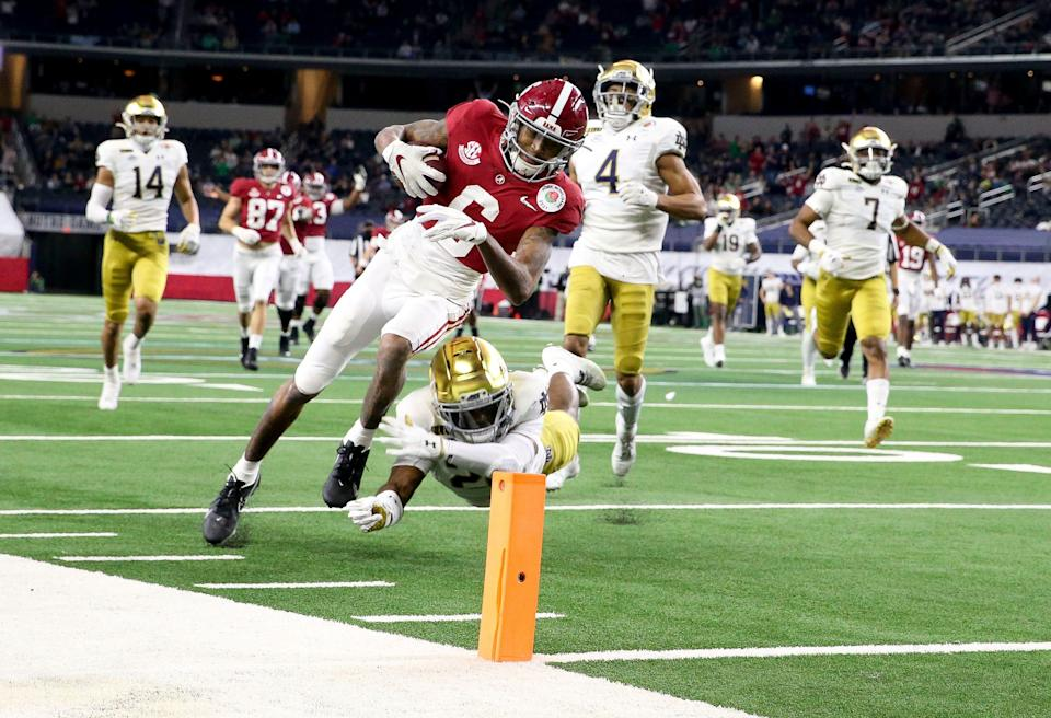 Alabama wide receiver DeVonta Smith dives over a tackle attempt by Notre Dame safety Shaun Crawford for a touchdown during the 2021 Rose Bowl in AT&T Stadium.