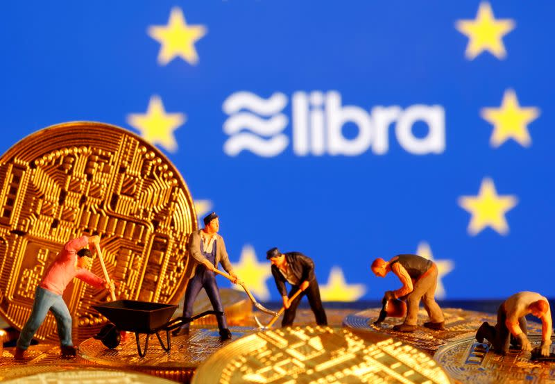 FILE PHOTO: Small toy figures are seen on representations of the virtual currency before the displayed European Union flag and the Facebook Libra logo in this illustration picture