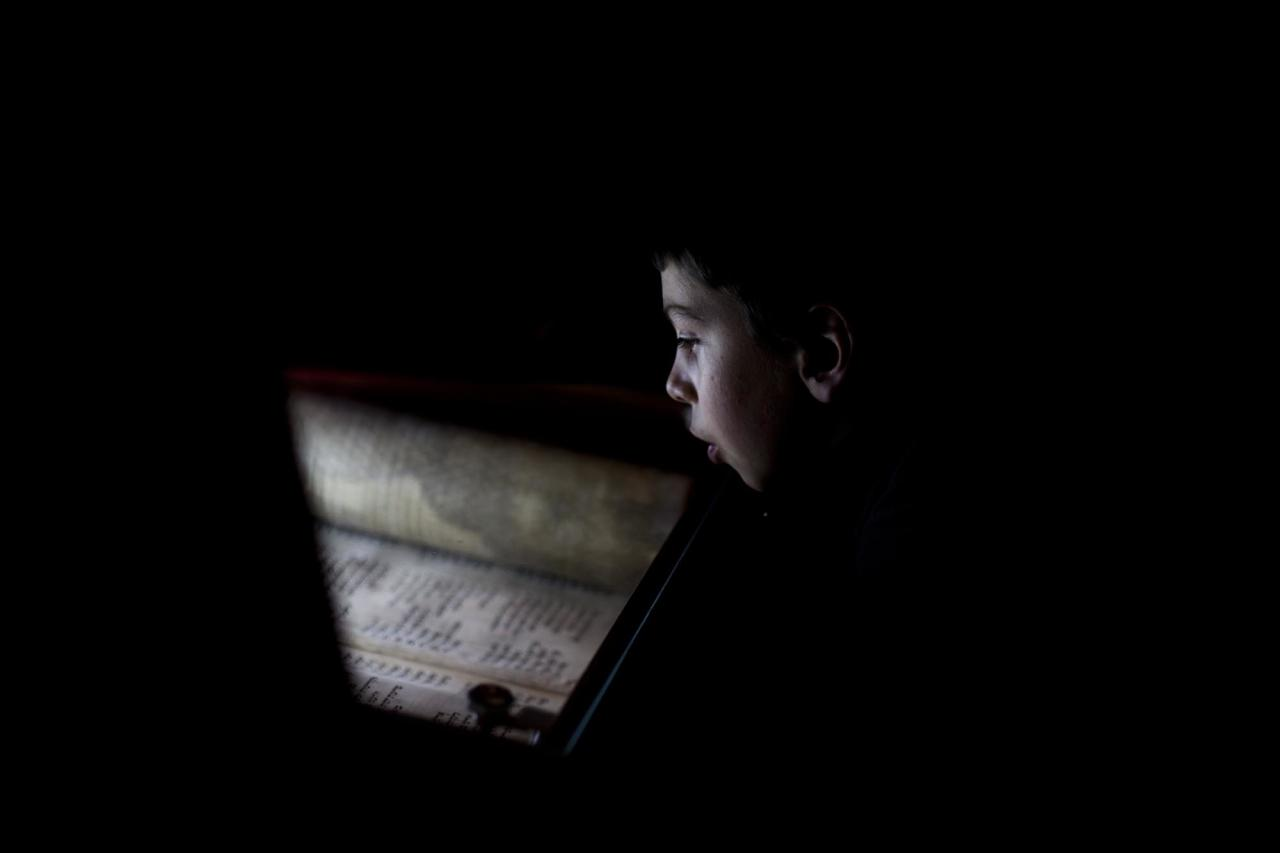 In this Friday, Jan. 27 2012 photo, a Jewish boy reads Torah scripts at the Western Wall, the holiest site where Jews pray, in Jerusalem's Old City. In a world overwhelmed by electronic gadgets that have changed the way we read, write and learn, the Jewish and Islamic arts of calligraphy have preserved their methods for generations. (AP Photo/Bernat Armangue)