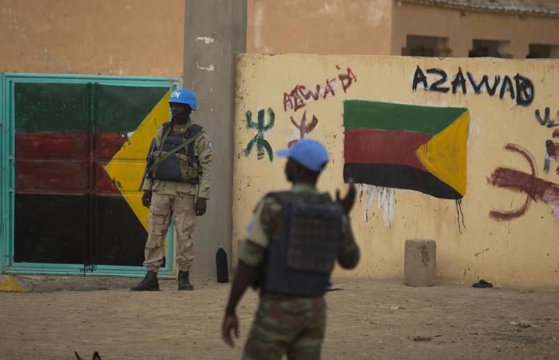 In this July, 27, 2013 photo, United Nations peacekeepers stand guard at the entrance to a polling station covered in separatist flags and graffiti supporting the creation of the independent state of Azawad, in Kidal, Mali. A bomb explosion killed several members of the U.N. peacekeeping mission in Mali in the troubled northern city of Kidal, a spokesman for the mission said Saturday, Dec. 14, 2013. (AP Photo/Rebecca Blackwell)