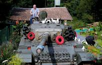 """Gary Blackburn, a 53-year-old tree surgeon from Lincolnshire, Britain, poses atop of a demilitarised Centurion tank he bought from the Swiss army at his British curiosities collection called """"Little Britain"""" in Linz-Kretzhaus, south of Germany's former capital Bonn, Germany, August 24, 2017. Picture taken August 24, 2017. REUTERS/Wolfgang Rattay"""