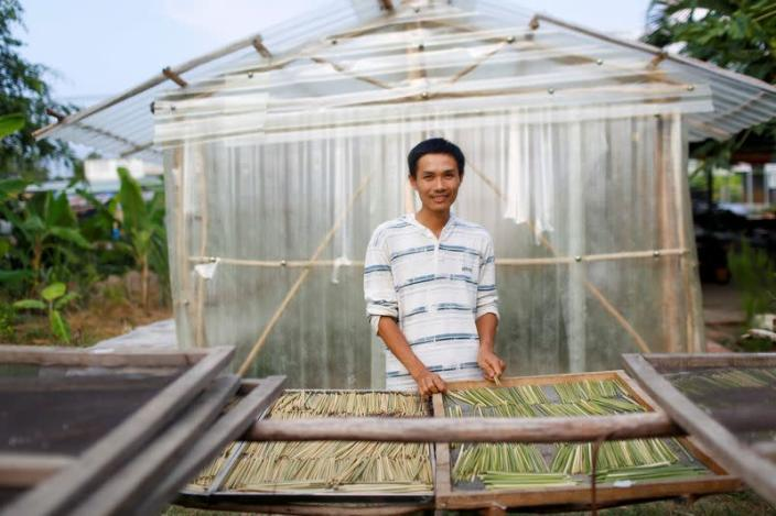 Tran Minh Tien, owner of 3T shop that makes grass straws, poses for a portrait in front of his workshop in Long An province