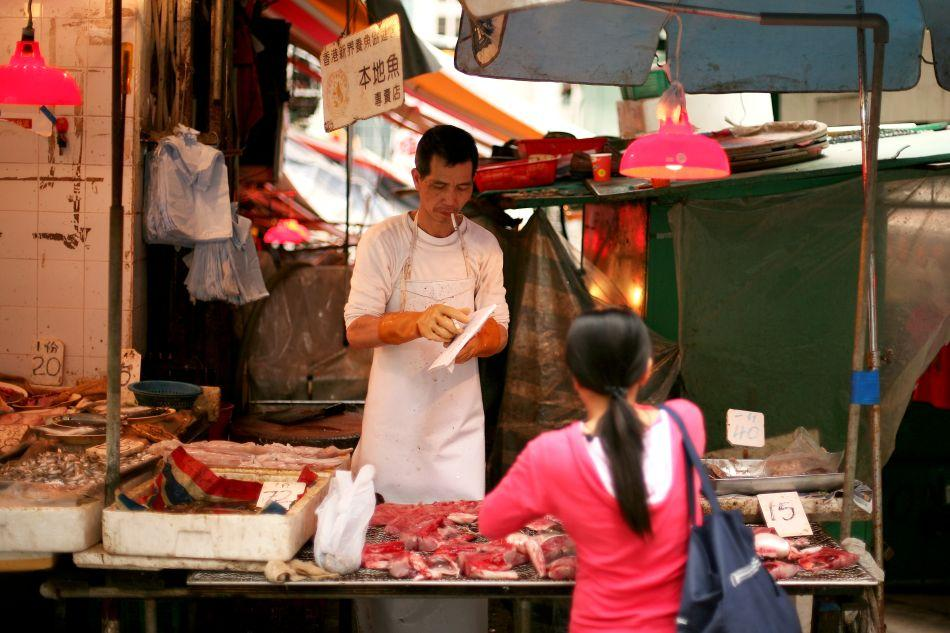 A butcher smokes a cigarette as he serves a customer from his street-side shop in Hong Kong.