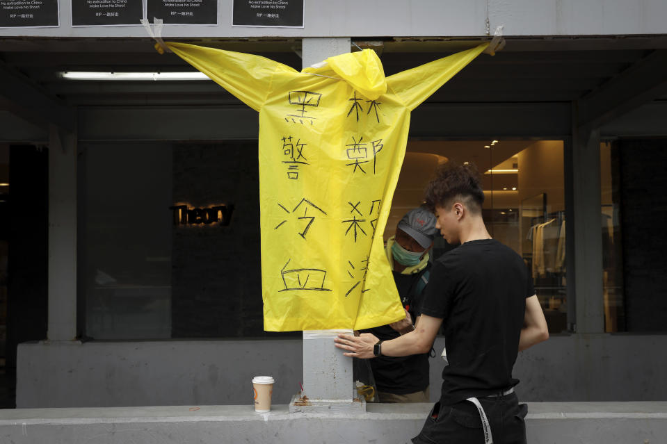 """Protesters place a raincoat bearing the words """"Cold blooded black police, Carrie Lam kill Hong Kong"""" on the site where a man fell to his death a day earlier after hanging a protest banner on the scaffolding of a shopping mall in Hong Kong, Sunday, June 16, 2019. Hong Kong was bracing Sunday for another massive protest over an unpopular extradition bill that has highlighted the territory's apprehension about relations with mainland China, a week after the crisis brought as many as 1 million into the streets. (AP Photo/Vincent Yu)"""