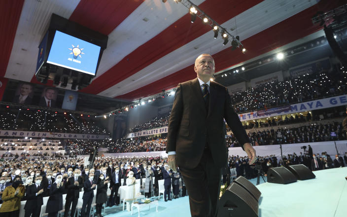 Turkey's President Recep Tayyip Erdogan arrives for a rally of his ruling party's congress inside a packed sports hall in Ankara, Turkey, Wednesday, March 24, 2021. Erdogan has come in the firing line for holding the rally inside the closed venue amid a new surge in COVID-19 cases. Thousands of party supporters filled the stands of the 10,400-capacity sports hall in the capital, in disregard of the government's own social distancing rules to fight the coronavirus pandemic. (Turkish Presidency via AP, Pool)