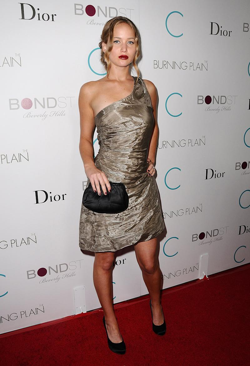 In Beverly Hills at the premiere of The Burning Plain Lawrence opted for a metallic one-shoulder dress, black satin pumps and a bold red lip for a bit of edge.