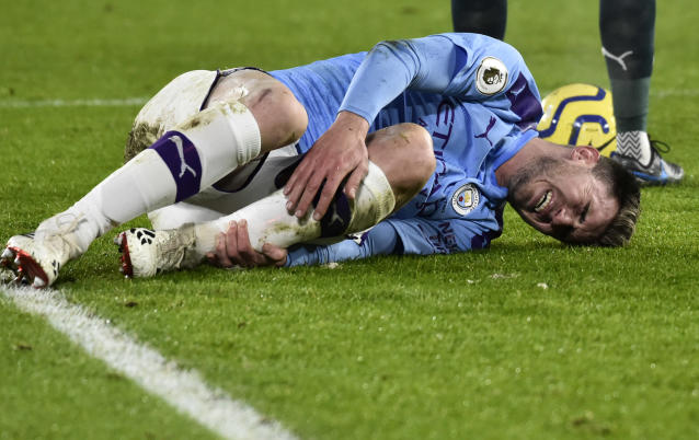 Manchester City's Aymeric Laporte lies on the pitch in pain during the English Premier League soccer match between Sheffield United and Manchester City at Bramall Lane in Sheffield, England, Tuesday, Jan. 21, 2020. (AP Photo/Rui Vieira)