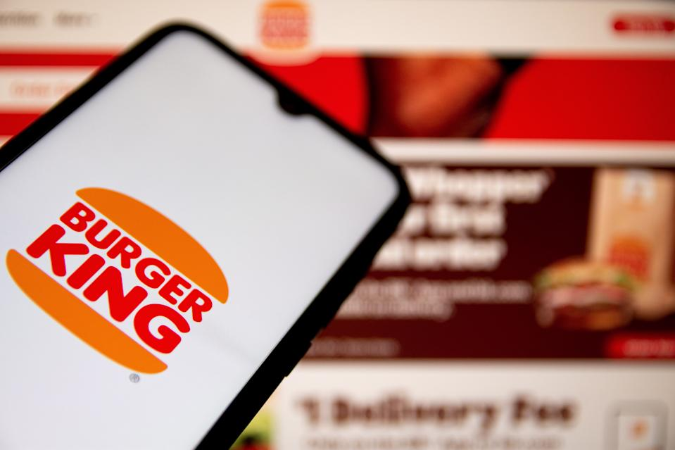 GREECE - 2021/05/07: In this photo illustration a Burger King logo seen displayed on a smartphone screen with Burger King website in the background. (Photo Illustration by Nikolas Joao Kokovlis/SOPA Images/LightRocket via Getty Images)