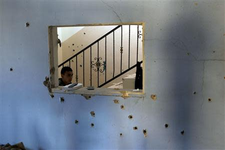 A boy walks past a bullet-riddled wall inside a house where Palestinian Hamas militant Hamza Abu Alhija was killed in the West Bank refugee camp of Jenin March 22, 2014. REUTERS/Mohamad Torokman