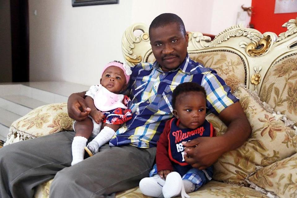 Kelly Chuunga, whose wife died after giving birth in Lusaka six months prior, poses with his twins Karen and Kelly junior at their grandmother's house in Lusaka on September 22, 2017 (AFP Photo/DAWOOD SALIM)